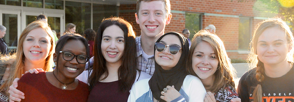 students posing together outside of the campus building
