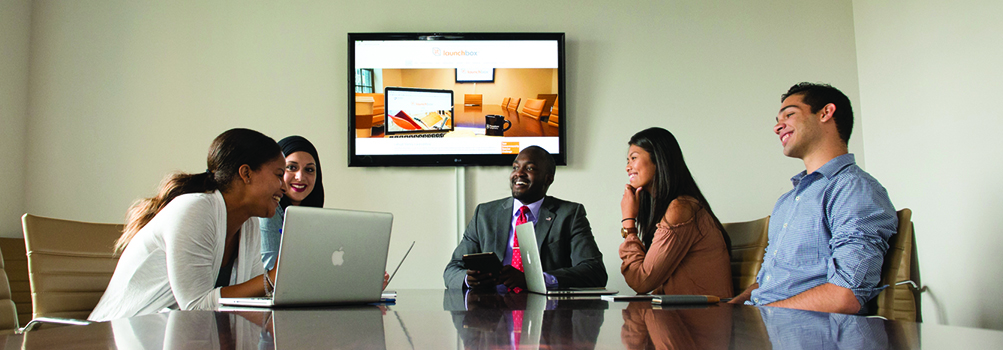 students meeting in the conference room with launchbox website on the screen