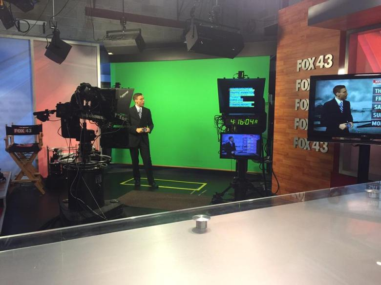 Weatherman in front of green screen in TV station.