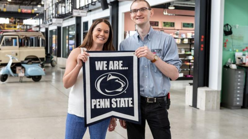 woman and man holding Penn State sign