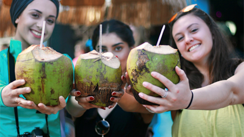 A group of students holding coconut drinks