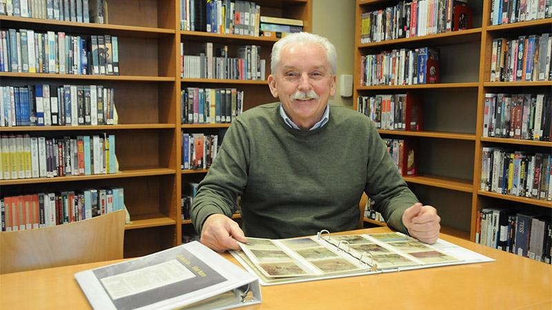 Tom Roney visiting PSU-LV library looks at his photo albums.