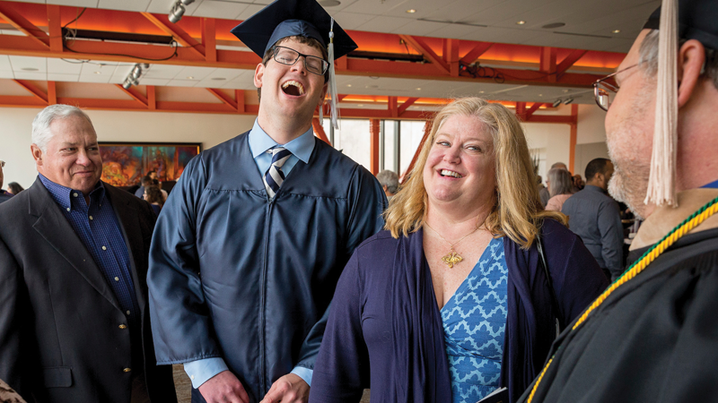 student in graduation cap and gown laughing with family