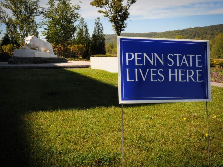 "sign reading ""penn state lives here"" in the ground in front of the penn state lehigh valley nittany lion shrine"