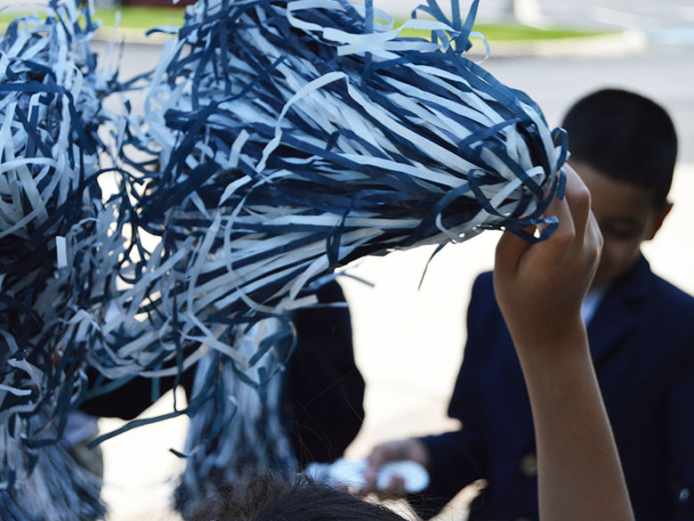 students shaking their blue and white pompoms