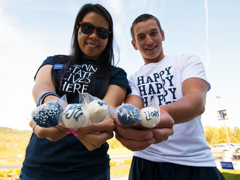 penn state alumni holding PSU-themed cake pops and smiling at the camera in their penn state gear