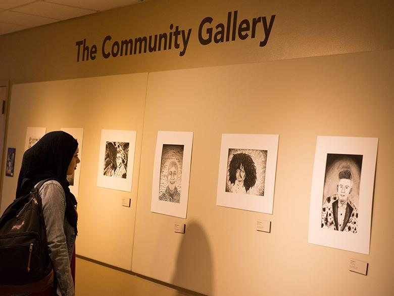 student viewing an exhibit in the community gallery
