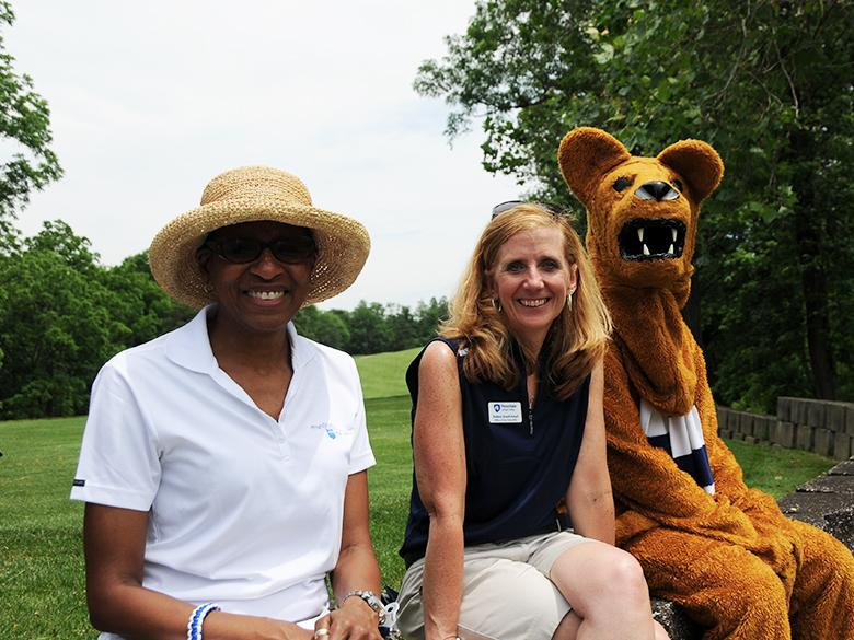 two staff members posing together with the nittany lion mascot