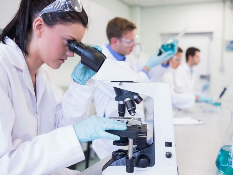 female student looking through laboratory microscope