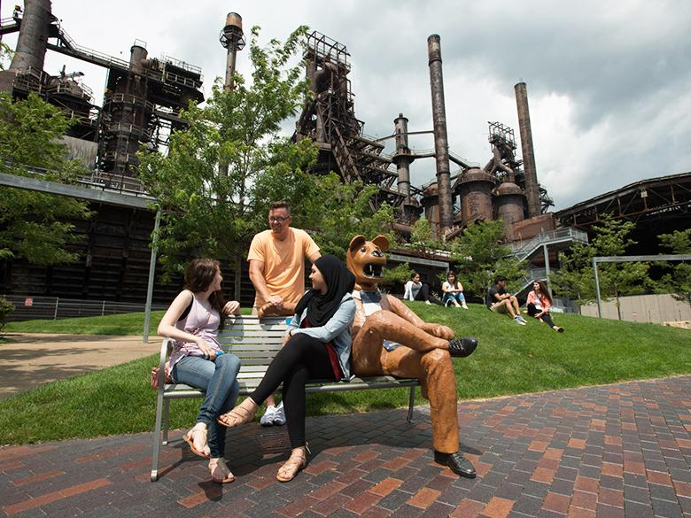 students hanging out in front of the steel stacks on the nittany lion bench