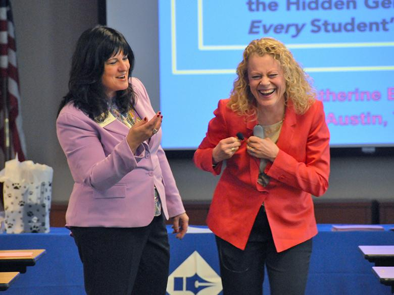 two professional development trainers are laughing together