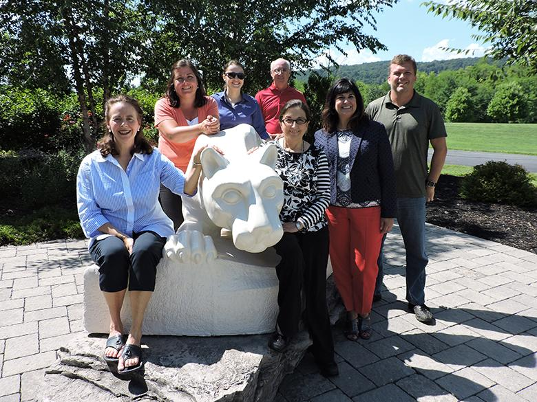 faculty and staff members posing with the nittany lion shrine