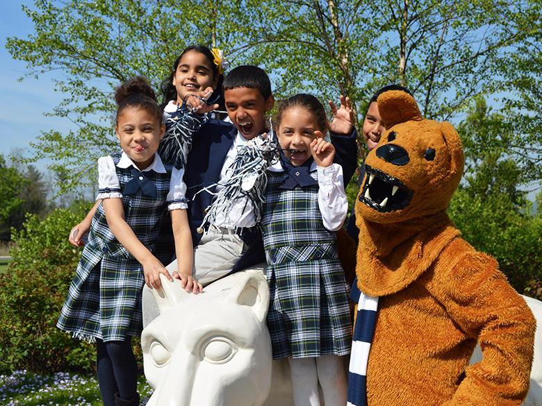 young children posing with the nittany lion shrine and the nittany lion mascot