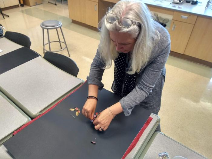 artist pinning insect wings on a board