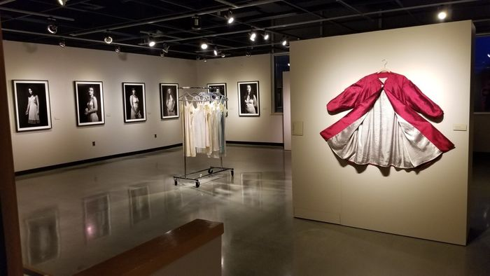 Art gallery featuring exhibit of photographs and clothing