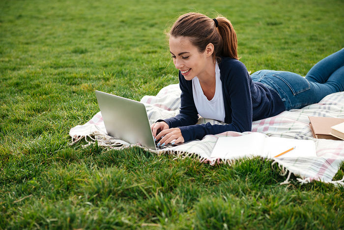 Happy teenage girl laying on blanket outside on the grass, typing on a laptop.