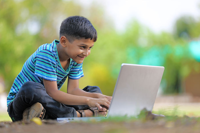 A happy young boy sitting cross-egged on the grass outside looking at the laptop computer