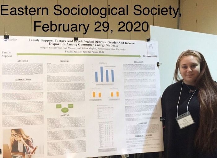 female student with her research poster