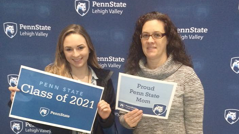 a student and parent pose with signs on Accepted Students Day