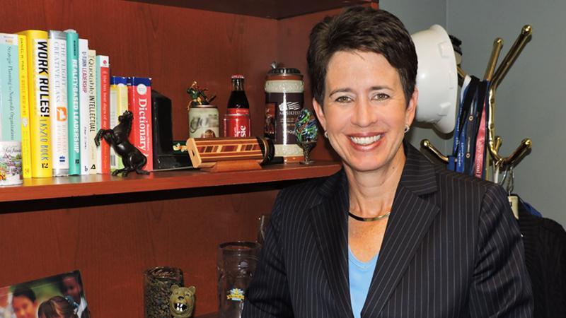 Kassie Hilgert poses in front of her bookshelf