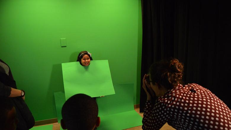 A little girl poses in front of green screen