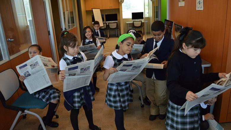 group of students reading newspapers