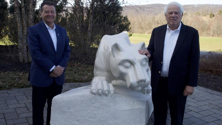 Two men flank Nittany Lion Shrine