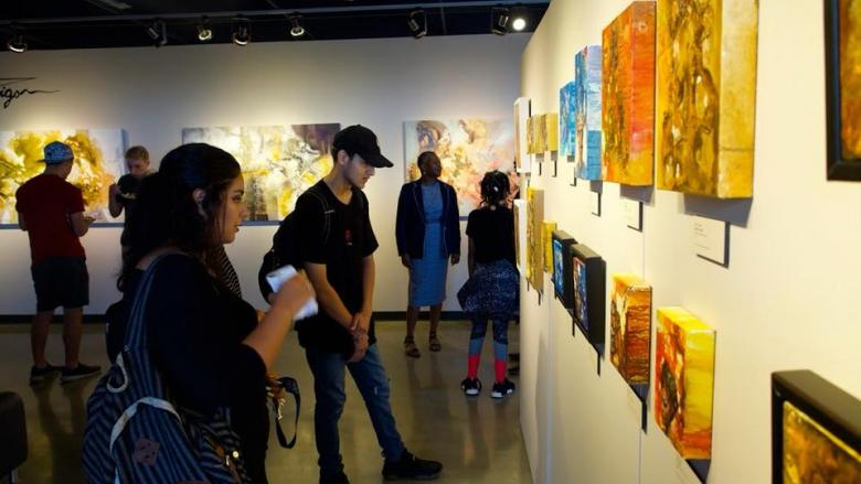 students viewing artwork on wall