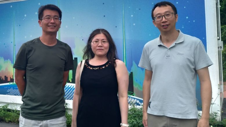 three people in front of lab facility in Taiwan