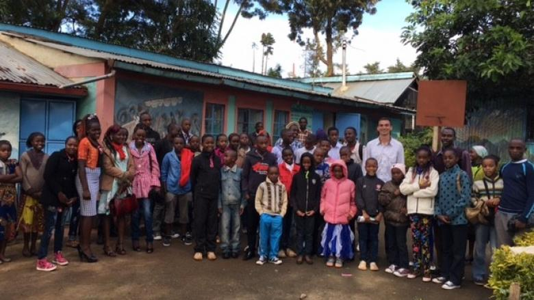 Nick Miller poses with children in Kenya