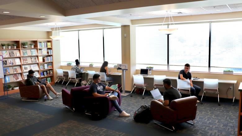 students studying in lounge chairs and desk chairs in library