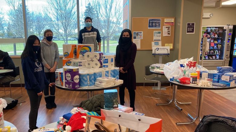 students separating donated items on tables