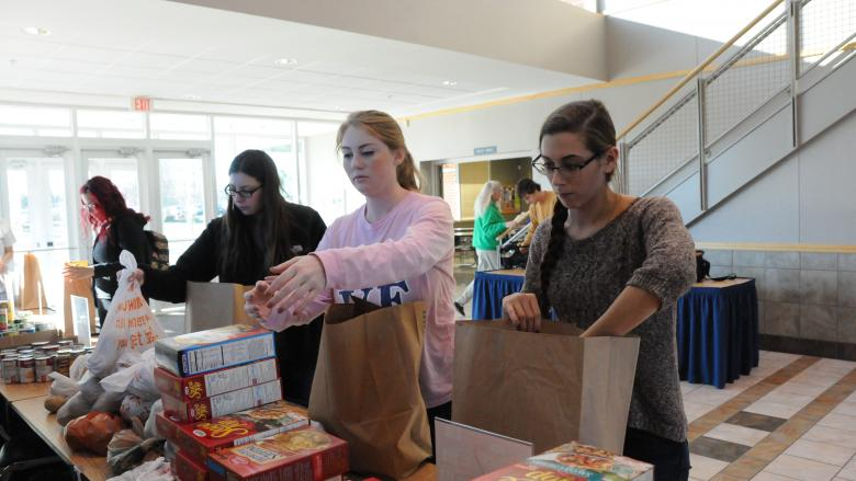 Students stuffing bags with food donations