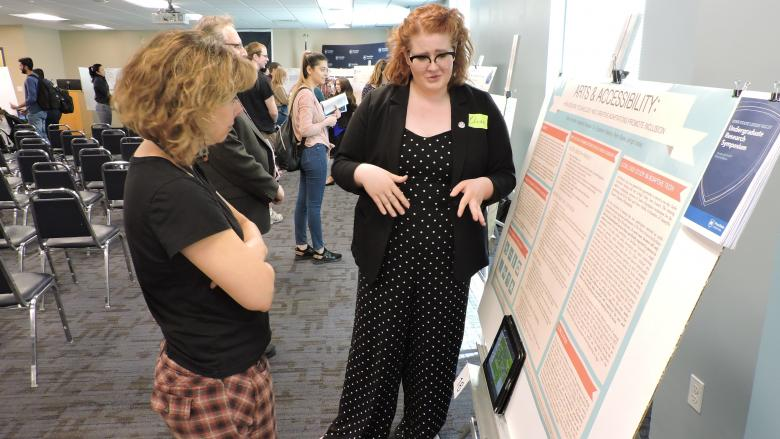 two women reviewing a research poster