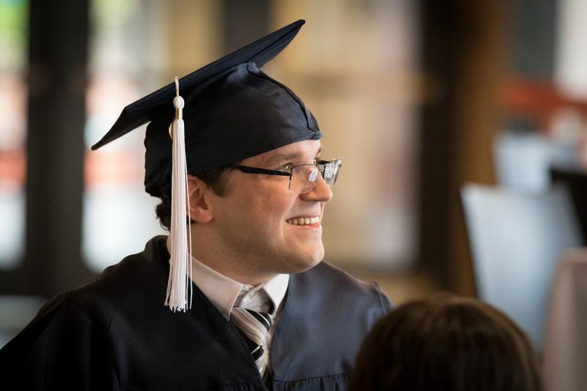 man with graduation cap on looking off into distance